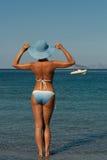 Donna in bikini sulla spiaggia che osserva lontano Fotografia Stock