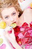 Donna sexy bionda giovane bella di tentazione in un bagno con i petali del fiore che morde pezzo di ritratto del primo piano del  immagine stock libera da diritti
