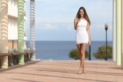 Donna sexy che cammina e che manda un sms sullo Smart Phone Immagine Stock