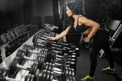 Donna sexy che fa allenamento con le teste di legno in palestra Fotografia Stock Libera da Diritti