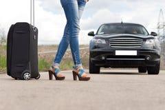 Donna che fa auto-stop con i suoi bagagli Immagini Stock Libere da Diritti
