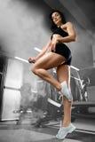 Donna sexy che fa gli esercizi in palestra Fotografia Stock