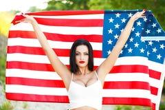 Donna sexy che giudica la bandiera degli S.U.A. all'aperto Immagini Stock