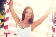 Donna sexy che giudica la bandiera degli S.U.A. all'aperto Fotografie Stock