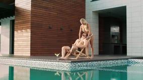 Donna sexy che massaggia uomo vicino alla piscina alla casa di lusso archivi video