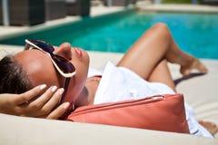 Donna sexy che prende il sole alla località di soggiorno dello stagno Fotografia Stock Libera da Diritti