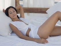 Donna che si rilassa nel letto a baldacchino Immagini Stock Libere da Diritti