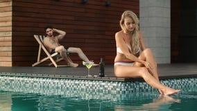 Donna sexy che si siede vicino alla piscina Ragazza graziosa che screma pelle vicino allo stagno stock footage