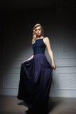 Donna sexy con capelli biondi lunghi in vestito blu scuro Immagine Stock