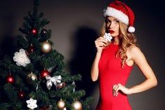 Donna sexy con capelli biondi ricci in Santa-cappello e vestito rosso Immagini Stock