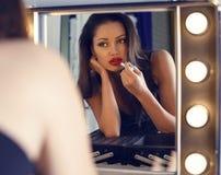 Donna sexy con capelli scuri che fanno trucco, esaminante lo specchio Immagini Stock