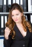 Donna sexy di affari con i dispositivi di piegatura nell'ufficio fotografia stock