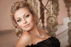 Donna bionda con i gioielli del diamante con l'acconciatura ed il trucco Fotografie Stock