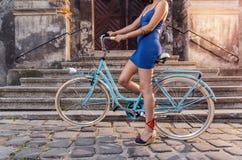 Donna sexy irriconoscibile in vestito blu sulla bicicletta Fotografia Stock Libera da Diritti