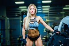Donna sexy muscolare della donna di forma fisica che si rilassa nella palestra Concetto dello stile di vita sano Bodybuilder in g immagini stock