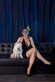 Donna sexy nei dres neri con il cane bianco Fotografia Stock Libera da Diritti