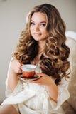 Donna sexy nel tè bevente dell'abito di mattina Capelli ondulati biondi, bello trucco, mattina delicata Ragazza che tiene una taz Fotografie Stock