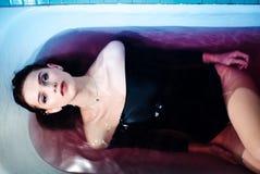 Donna sexy nella tuta nel bagno Luce intensa ed acqua colorata Spalle nude immagine stock