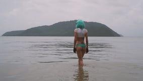 Donna sexy nello stile futuristico moderno con la parrucca blu che posa nel mare immagini stock