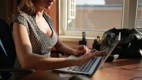 Donna sexy pettoruta di affari che lavora per un computer portatile archivi video