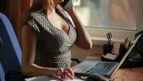 Donna sexy pettoruta di affari che lavora per un computer portatile Comunicando sul telefono stock footage