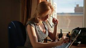 Donna sexy pettoruta di affari che lavora per un computer portatile succhia i vetri archivi video