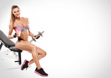 Donna sexy piacevole che si siede su un banco e su un allenamento con la testa di legno Fotografia Stock