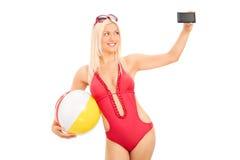 Donna sexy in un costume da bagno che prende un selfie Immagini Stock