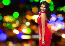 Donna sexy in vestito rosso sopra le luci notturne Immagine Stock