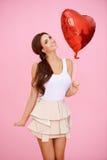 Donna vivace con il pallone del cuore Fotografia Stock