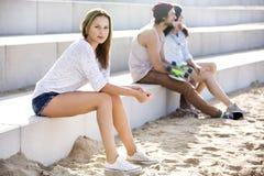 Donna sicura che si siede sui punti alla spiaggia fotografia stock libera da diritti