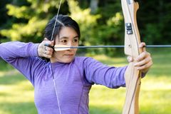 Donna sicura che tende con l'arco e la freccia in foresta Fotografie Stock Libere da Diritti