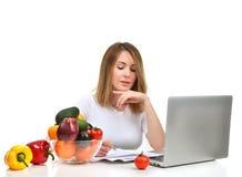 Donna sicura del dietista che lavora allo scrittorio con la frutta fresca a Fotografia Stock