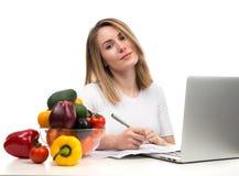 Donna sicura del dietista che lavora allo scrittorio con la frutta fresca a immagini stock libere da diritti