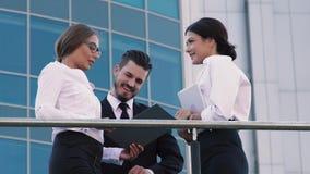 Donna sicura di affari che mostra la sua ricerca a una coppia di gente di affari Offre discuterla insieme stock footage