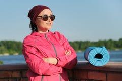 Donna sicura di mezza età di sport con la stuoia di yoga e la bottiglia di acqua con le armi piegate attraversate fotografia stock libera da diritti