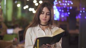 Donna sicura nell'usura convenzionale della blusa bianca che redige informazioni in suo taccuino in ufficio o caff? moderno Fondo video d archivio