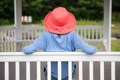 Donna snella in cappello rosa scuro che si siede sul banco bianco in gazebo che esamina il suo giardino immagini stock