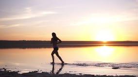 Donna snella con capelli lunghi che corre all'aperto Pareggiando dall'acqua seaside Il Sun splende sui precedenti video d archivio