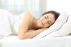 Donna soddisfatta che dorme in un letto comodo immagine stock