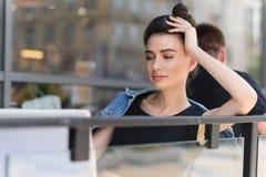 Donna soddisfatta che si siede su un terrazzo Fotografia Stock Libera da Diritti