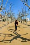 Donna sola che cammina attraverso una passeggiata piacevole su una mattina soleggiata di inverno a Calella de La Costa, spiaggia  Immagine Stock