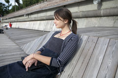 Donna sola che si siede dal fiume immagine stock