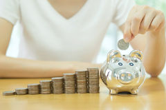 Donna soldi giovane di risparmio che mette una moneta in un salvadanaio Fotografia Stock Libera da Diritti