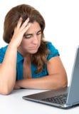 Donna sollecitata che esamina il suo computer Immagini Stock Libere da Diritti
