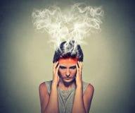 Donna sollecitata che pensa vapore troppo duro che esce su della testa Immagini Stock