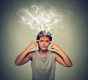 Donna sollecitata che pensa vapore troppo duro che esce su della testa Fotografie Stock Libere da Diritti
