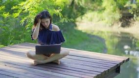 Donna sollecitata che per mezzo del computer portatile sul molo di legno archivi video