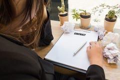 Donna sollecitata che si siede allo scrittorio di legno con il capitolato d'oneri e Fotografia Stock