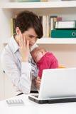 Donna sollecitata con il bambino che lavora dalla casa Fotografia Stock